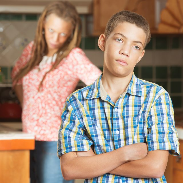 Teenaged son stands with arms crossed in the kitchen after having disagreement with him mother