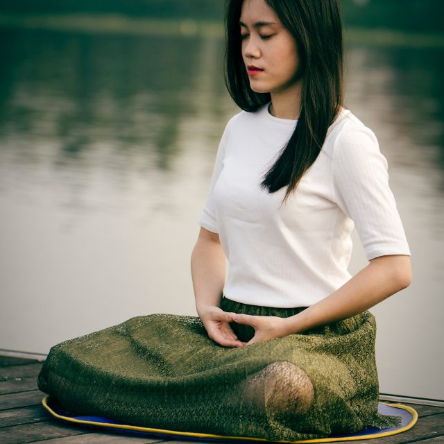 woman meditating near water